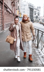 Pretty couple in love are walking on the street in winter. Fashion style portrait.