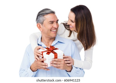 Pretty couple offering present to husband on white background