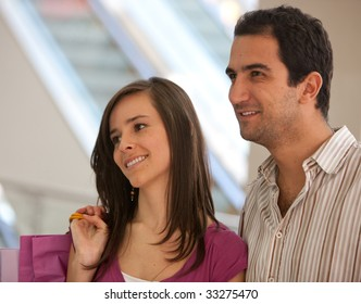 pretty couple shopping looking at a window and smiling