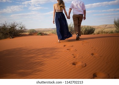 A pretty couple walks hand in hand on the red sand dunes in the kalahari region of south africa