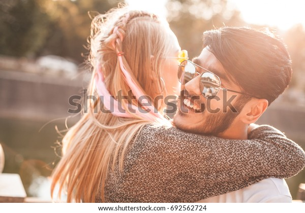 Pretty couple is whirling on the street under the sunlight.