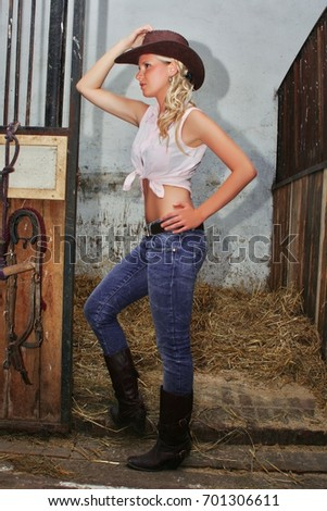 c6710bf86 Pretty cowgirl in brown hat posing in the horse stable looking sideways.  View Preview