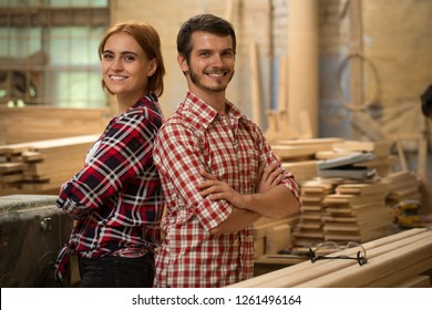 Pretty craftswoman with ginger hair and handsome craftsman posing in joiner's shop. Bearded joiner and beautiful woman smiling and looking at camera. Team wearing in checked shirts.