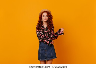 Pretty curly girl in boater, bright blouse and blue skirt moves on isolated orange background