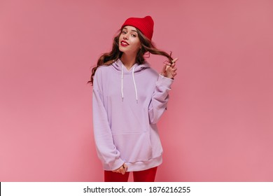 Pretty curly girl in red hat and purple oversized hoodie smiles on pink background. Charming woman coquettishly plays hair on isolated.
