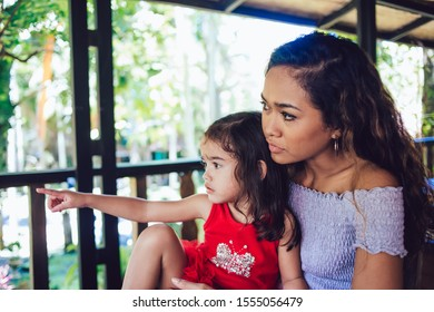 Pretty curly Indonesian woman and cute little girl in red dress sitting on resort cafe terrace against tropical trees looking away