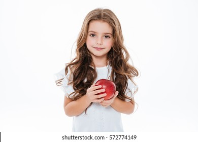Pretty curly little girl standing and holding red apple over white background