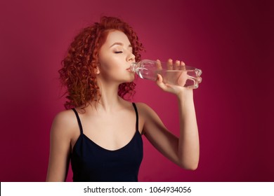 Pretty curly redhead healthy young woman drinking pure mineral bottled water on a red background