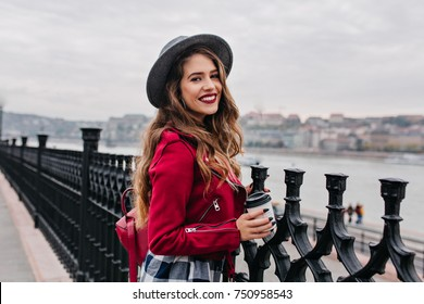 Pretty curly woman with bright makeup enjoying city view from bridge in autumn day. Lovely brunette woman in red jacket spending time on embankment during rest in Europe.