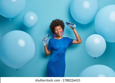 Pretty curly woman chills at party, dances happily, keeps hands raised with shoes, spends time in night club, takes off high heel shoes, poses against blue wall. Monochrome shot. Holiday, celebration