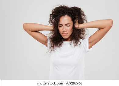 Pretty curly woman covered his ears over gray background