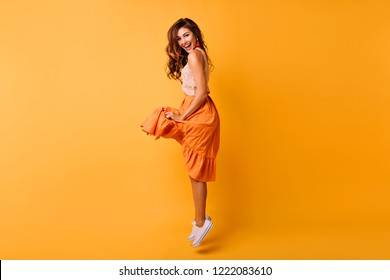 Pretty curly woman in orange skirt jumping with smile. Amazing european lady in summer outfit posing in front of yellow wall.