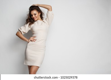 Pretty, cute, adorable young woman with makeup, wavy brown hair and smile on her face in the beautiful dress is posing in the studio, white background, fashion style