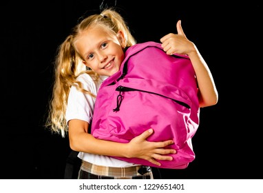 Pretty cute blonde hair girl with a pink schoolbag looking at camera showing thumb up gesture happy to go to school isolated on black background in back to school and children education concept.