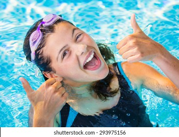 Pretty cute brunette with her thumbs up in a pool