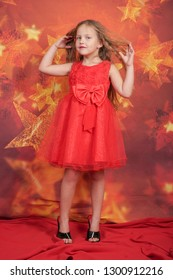 pretty cute caucasian child girl in red evening dress and mother's high heels standing on orange background with stars