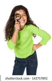 Pretty cute caucasian girl wearing a green long sleeve top and blue jeans. She is playing with a magnifying glass.