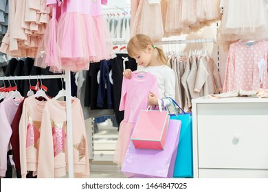 Pretty, cute girl holding shopping bags and choosing clothing in department store. Child looking at pink beautiful dress. Many pink clothes on hangers. Concept of stylish children clothing.