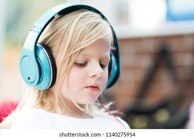 A pretty cute little girl blonde listens to her music with over the ear headphones, trademark removed