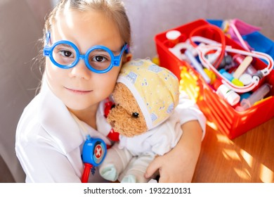 Pretty cute preschool child girl wearing in white medical uniform playing with sick teddy bear toy as patient in hospital game