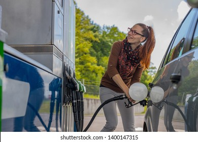 Pretty cute redheaded woman filling her car with gasoline on a petrol station. Happy woman refueling car looking at the machine.
