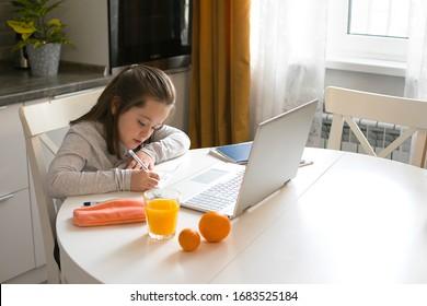 Pretty cute schoolgirl studying at home using laptop. Coronavirus home school, online education, home education, quarantine concept. Stay at home
