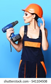 pretty cute sexy builder girl or brunette woman with fashion makeup on serious face in orange uniform with hard hat or helmet holding electric screwdriver on blue studio background