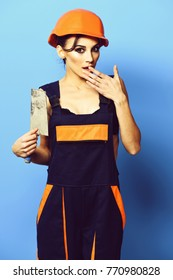 pretty cute sexy builder girl or brunette woman with fashion makeup on surprised face in orange uniform with hard hat or helmet holding tool or putty knife on blue studio background