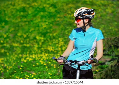 Pretty cyclist girl looking to the green lawn