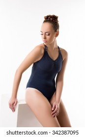 Pretty dancer in blue bodysuit. Studio photo