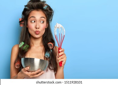 Pretty dark haired Japanese housewife whips cream in steel bowl, makes cake in kitchen, keeps lips rounded, wears curlers and nightgown, tries new culinary recipe, isolated on blue background