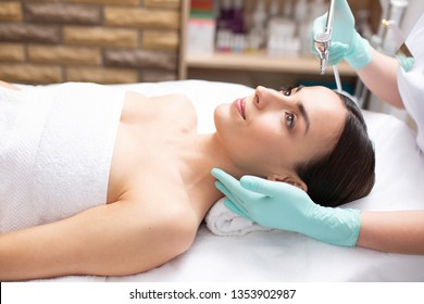 Pretty dark haired young lady lying on the medical couch and looking glad while dermatologist holding metal tool for oxygen spray treatment