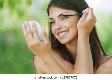 Pretty dark-haired funny young woman dyes her eyelashes, against background of summer green park.