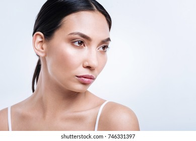 Pretty dark-haired woman posing with an intimidating look