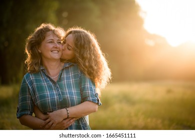 Pretty daughter embracing her mother from behind and kissing