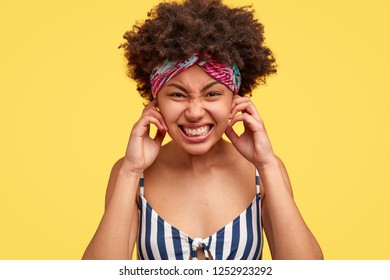 Pretty displeased dark skinned woman pluggs ears, annoyed with terrible noise, demands silence and calm atmosphere, clenches teeth, wears headwear and striped top, isolated over yellow wall.