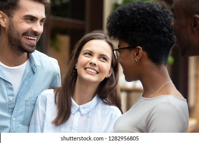 Pretty diverse girls and guys best friends standing outdoor talking joking laughing feels good and happy. Friendship between multiracial young people warm relations amity and racial tolerance concept