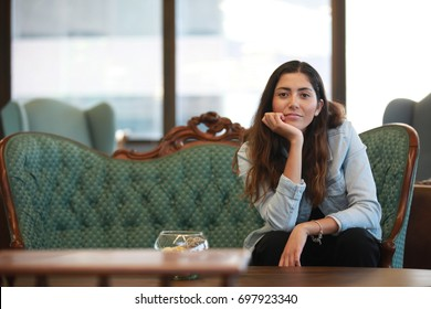 Pretty dreamy woman leaning on hand and dreaming sitting on sofa in the office