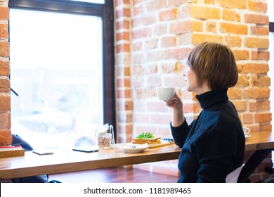 Pretty drinking coffee in a cafe. young woman in business clothes on a lunch break