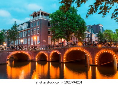 Pretty dutch doll houses and bridges illuminated and reflected along the tranquil canals of Amsterdam.