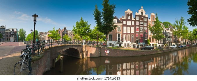 Pretty dutch doll houses and house boats reflected in the tranquil canals of Amsterdam, Holland.