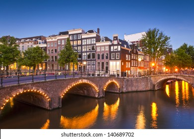 Pretty dutch doll houses illuminated and reflected along the tranquil canals of Amsterdam.