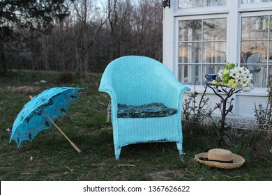Pretty Edwardian Era scene of blue wicker chair and parasol in garden at twilight