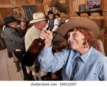Pretty elderly red head with liquor bottle in old saloon