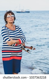 Pretty elderly woman in sunglasses on vacation by sea on background of ship