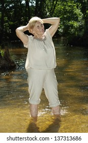 Pretty elderly woman went to the river to relax