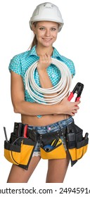 Pretty electrician in helmet, shorts, shirt, tool belt with tools holding an electric cable, smiling. Isolated over white background