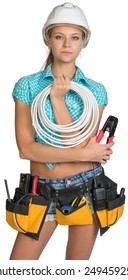 Pretty electrician in helmet, shorts, shirt, tool belt with tools holding an electric cable. Isolated over white background