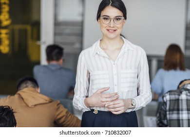 Pretty elegant Caucasian smiling woman teacher standing at classroom and looking at camera.