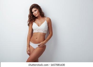 Pretty elegant lady in beautiful lingerie against grey background